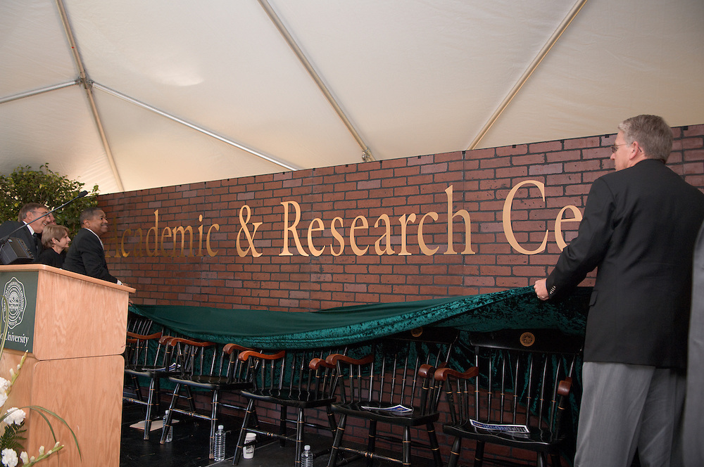18414Academic & Research Center Groundbreaking September 29, 2007..Stuckeys and Vincent pulling cord on curtain to reveal the ?name? on a faux brick wall