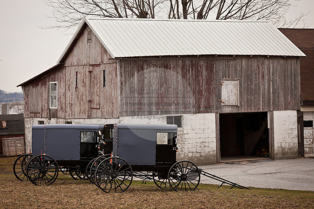 Amish horse buggies parked by an old barn in Gordonville, PA.