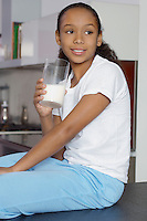 Girl (7-9) drinking milk, indoors