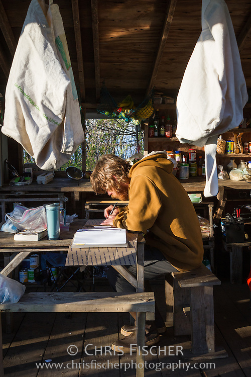 Biologist John Gorey works at a table in the outdoor kitchen at base camp on Stratton Island, Maine. John is the field station co-supervisor for National Audubon Society's Seabird Restoration Program on Stratton Island, Maine.