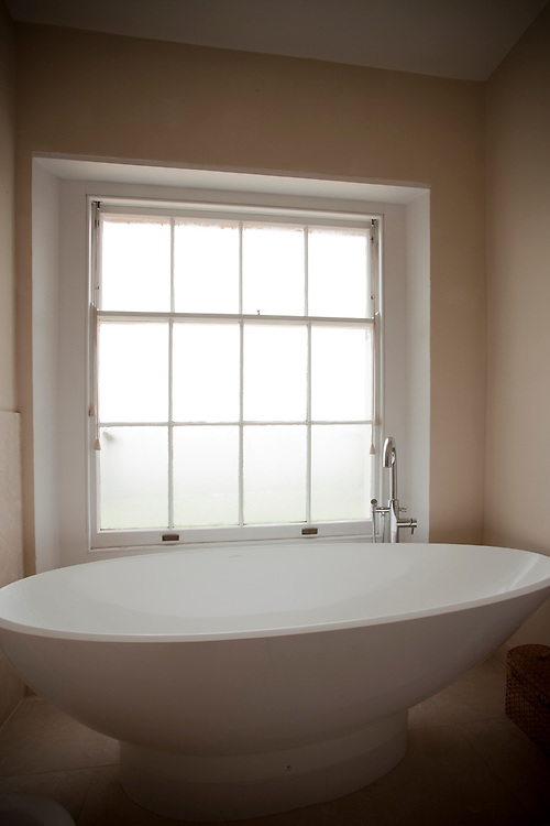 Elegant oval bathroom interior with bath in front of window with mixer tap, no people