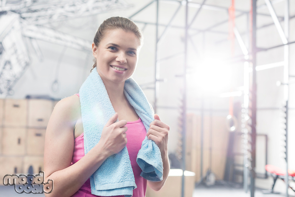 Portrait of happy woman holding towel around neck in crossfit gym