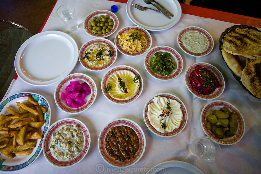 A colorful selection of local dishes in a Palestinian restaurant in Abu Dis, just outside the barrier near East Jerusalem, includes hummus, olives, chiles, beets, cabbage slaw, and baba ganoush.