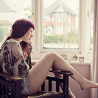 Full body portrait of a young demale with long red hair wearing a floral blouse, sitting on a chair by the window, looking contemplative.