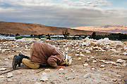 A man of faith prays on the bare ground. Dec. 10, 2013. West Bank, Palestinian Territories. (Photo by Gabriel Romero/Alexia Foundation ©2014)