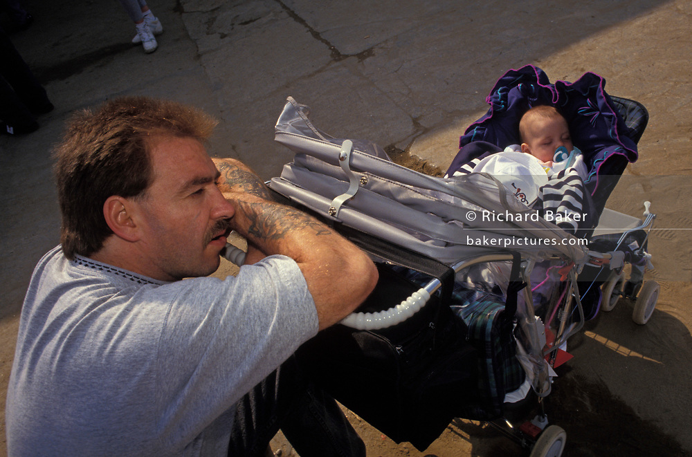 A father rests his head on tattooed arms while minding his baby, asleep in its buggy on the promenade at the north-eastern seaside resort of Scarborough, on 21st August 1992, in Scarborough, England.