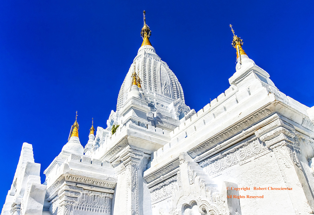 Lay Myet Hnar Complex: A wide angle lens provides a striking low angle angle view of the white main Buddhist Wat at the Lay Myet Hnar Complex as it shoots skyward, set against a vibrant clear blue sky, Bagan Myanmar.