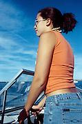 Teenage girl steers a boat.