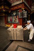 A worker pushes a food cart through the Yu Yuan bazaar in Shanghai, China