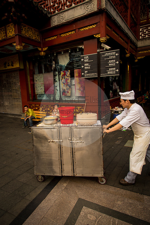 A worker pushes a food cart through the Yu Yuan bazaar in Shanghai, China