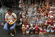 "A woman eats pancit (noodles) as she waits for buyers of any of her hundreds of Santo Niño and other religious statues during the Philippines festival of the Santo Niño. Many Filipinos in this predominantly Catholic population have similar statues, which they parade through the streets once a year. The tourism department of the Philippines calls Metro Manila's Santo Niño Festival ""a grand procession of over 200 well-dressed images of the child Jesus."" (Supporting image from the project Hungry Planet: What the World Eats) The family of Angelita Cabaña of Manila has their own Santo Niño statue in the living room of their small home."
