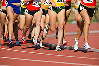 Women track runner legs run in a pack during a track and field event around a race track.