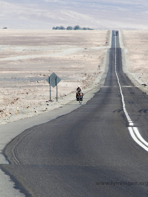 Long distance cyclist biking by Panamerican Highway through teh Atacama desert, Chile