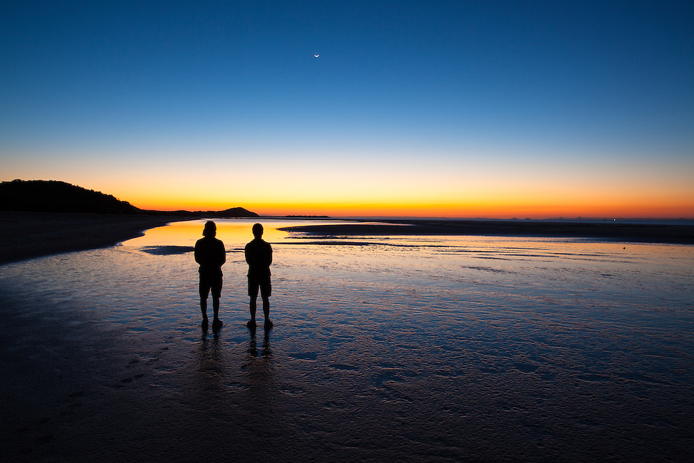 Two men stand out on the beach at North Point, Moreton Island, watching the light fade from the sky and the crescent moon set at twilight.