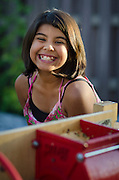 A young girl enjoys the autumn tradition of apple cidar pressing, Durango, CO.