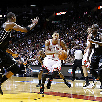 29 January 2012: Chicago Bulls point guard Derrick Rose (1) drives past Miami Heat center Joel Anthony (50) and Miami Heat power forward Chris Bosh (1) during the Miami Heat 97-93 victory over the Chicago Bulls at the AmericanAirlines Arena, Miami, Florida, USA.