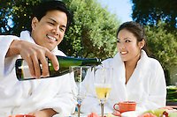 Chinese couple wearing bathrobes, drinking champagne at outdoor table