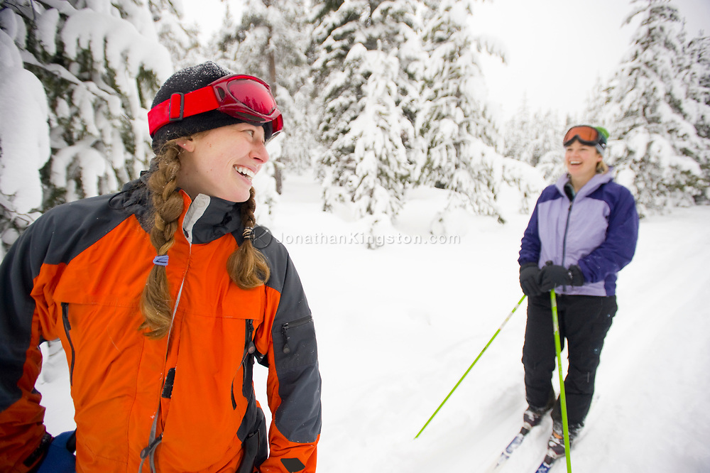 Two young women laughing on cross country skis on a trail in the snow in Bend, Oregon. (releasecode: jk_mr1033, jk_mr1032) (Model Released)