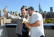 "Lance Bass, left, Joey Fatone and the Aflac Duck take a ""selfie"" and enjoy the New York City skyline, Monday, Sept. 23, 2013, during Advertising Week.  The Aflac Duck is celebrating his comeback from injuries that left him unable to quack.  (Photo by Diane Bondareff/Invision for Aflac/AP Images)"