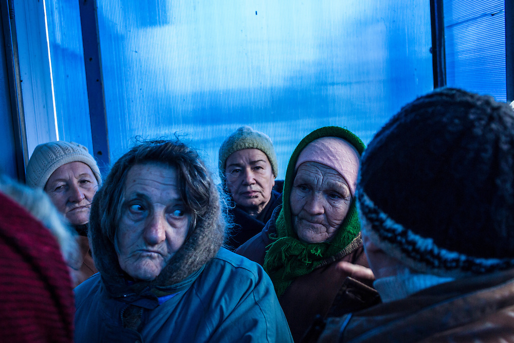 Local residents line up to receive aid delivered by the ICRC on Friday, December 11, 2015 in Troitske, Ukraine.