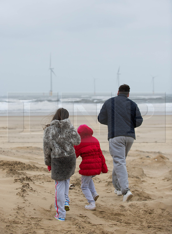 © Licensed to London News Pictures. 23/03/2013..Cleveland, England..A family run onto a windswept beach at Redcar as the wintery weather continues to chill the country. Cleveland on the east coast of England suffered freezing cold and strong winds that brought big seas to the coastline...Photo credit : Ian Forsyth/LNP