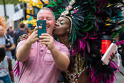 London, August 29th 2016. A member of the public gets a selfie with one of the participants in the procession during day two of Europe's biggest street party, the Notting Hill Carnival.