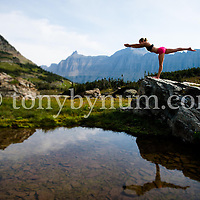 woman yoga balance on rock above lake in dramatic mountians