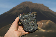 Hand holding piece of cold lava, vulcano in background. Fogo. Cabo Verde. Africa.