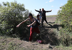 © London News Pictures. Migrants jump over a ditch trying to avoid the police close to the Hungarian and Serbian border town of Roszke, Hungary, September 8 2015. The UN's humanitarian agencies are on the verge of bankruptcy and unable to meet the basic needs of millions of people because of the size of the refugee crisis in the Middle East, Africa and Europe, senior figures within the UN have told the media.   Picture by Paul Hackett /LNP