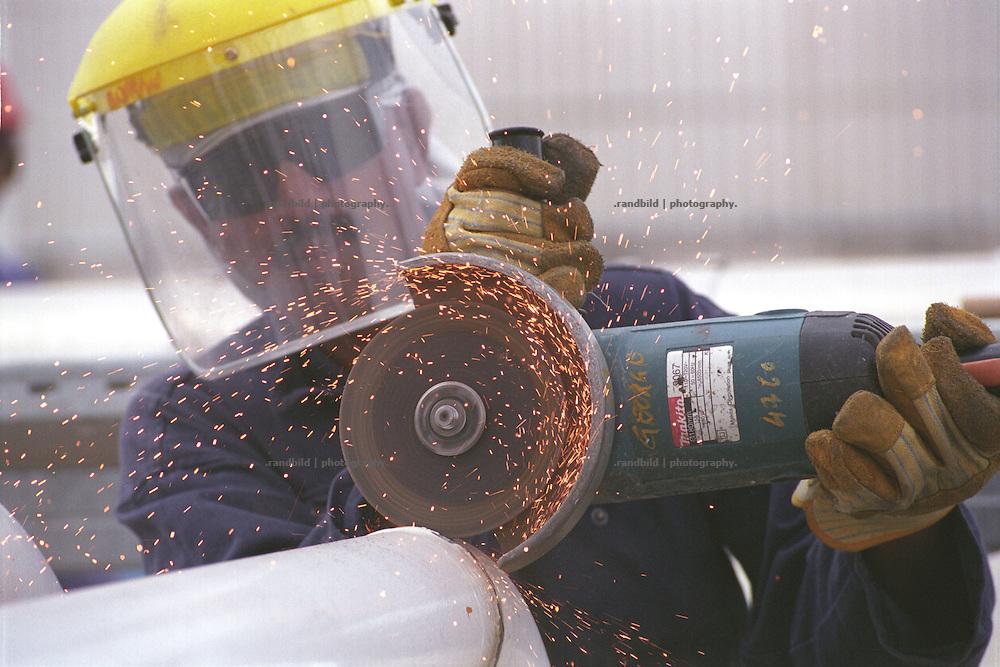 Ein indischer Arbeiter flext an einem Rohr in der ostgeorgischen BTC Pipeline Pumpstation bei Rustawi. Die Pumpstation ist eine von insgesamt acht, die kaspisches Oel durch die 1800 Kilometer lange BTC Pipeline an die tuerkische Mittelmeerkueste pumpen sollen...An indian worker in the pump station of the BTC pipeline near Rustavi, Georgia.