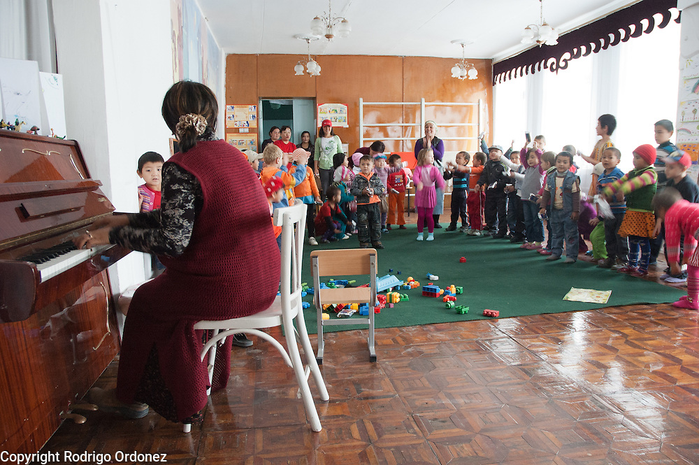 A teacher plays the piano while children dance at Kindergarten 29, in Osh (Kyrgyzstan), where Save the Children supports a child-friendly space.