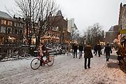 Winkelend publiek loopt door de sneeuw in Utrecht