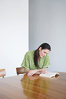Mid adult woman sitting at table reading book