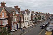 Aerial view of a holidaying couple walking with vacation baggage on Marshall Street, on 14th July 2017, at Bridlington, East Riding, England.