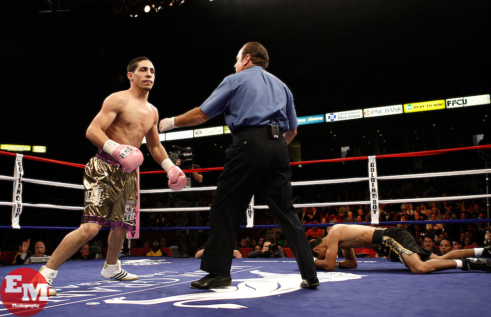 Dec 2, 2009; Philadelphia, PA, USA; Danny Garcia (gold trunks) knocks down Enrique Colin (black trunks) during their bout at the Liacouras Center.