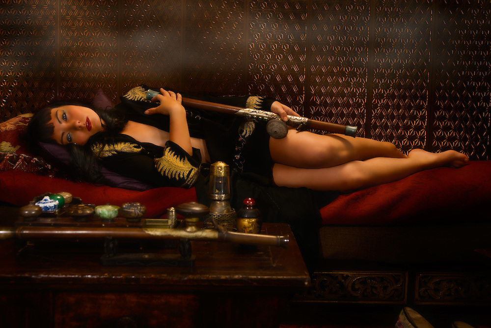 "Am I not desirable? Seductive, beautiful woman portrayed by alternative model Sabrina Sin, smoking opium in an ornate pipe, a forbidden pleasure among the liberated French females of the 1930's. She is being carried away by the effects of this forbidden pleasure surrendering herself to the effects of the drug. This collection was inspired by the writings of Brassai in his book ""The Secret Paris of the 1930's""."