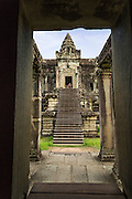 """02 JULY 2013 - ANGKOR WAT, SIEM REAP, SIEM REAP, CAMBODIA:  Looking into Angkor Wat from a portal on the north side of the temple. Angkor Wat is the largest temple complex in the world. The temple was built by the Khmer King Suryavarman II in the early 12th century in Yasodharapura (present-day Angkor), the capital of the Khmer Empire, as his state temple and eventual mausoleum. Angkor Wat was dedicated to Vishnu. It is the best-preserved temple at the site, and has remained a religious centre since its foundation– first Hindu, then Buddhist. The temple is at the top of the high classical style of Khmer architecture. It is a symbol of Cambodia, appearing on the national flag, and it is the country's prime attraction for visitors. The temple is admired for the architecture, the extensive bas-reliefs, and for the numerous devatas adorning its walls. The modern name, Angkor Wat, means """"Temple City"""" or """"City of Temples"""" in Khmer; Angkor, meaning """"city"""" or """"capital city"""", is a vernacular form of the word nokor, which comes from the Sanskrit word nagara. Wat is the Khmer word for """"temple grounds"""", derived from the Pali word """"vatta."""" Prior to this time the temple was known as Preah Pisnulok, after the posthumous title of its founder. It is also the name of complex of temples, which includes Bayon and Preah Khan, in the vicinity. It is by far the most visited tourist attraction in Cambodia. More than half of all tourists to Cambodia visit Angkor.         PHOTO BY JACK KURTZ"""