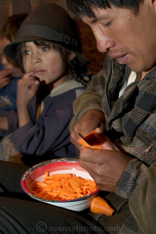 (MODEL RELEASED IMAGE). Orlando Ayme helps his wife in their detached kitchen house cut carrots for soup in Tingo, Ecuador. (Supporting image from the project Hungry Planet: What the World Eats.)