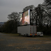 At the edge of an expansive parking lot serving Leopardstown Racecourse, a horse-racing venue in south Dublin, a 50 m square screen stands high ahead of another drive-in theatre session. Dublin, Ireland - March 23, 2020.