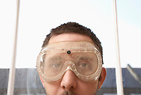 Man wearing protective eye goggles near window close up high section