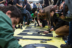 ter, London, May 30th 2015. Anti-austerity campaigners bring traffic on Westminster Bridge as they paint and hang a banner off the bridge highlighting an alleged £120 billion owed in taxes as compared to the proposed £12 billion cuts to welfare. PICTURED: Protesters paint their banner on Westminster Bridge, bringing traffic chaos to the area.