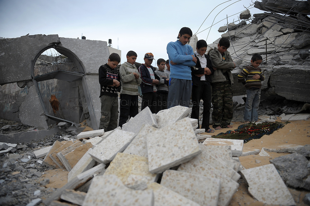 Palestinian children perform the Friday noon prayer on the rubble of an Israel-bombed mosque in Gaza City on January 23, 2009. Israeli Prime Minister Ehud Olmert has put the justice minister in charge of defending Israel against charges of war crimes during its 22-day Gaza assault. According to the Palestinian central bureau of statistics, 20 mosques were among the over 4000 buildings that were destroyed since the December 27 start of Israel's offensive.