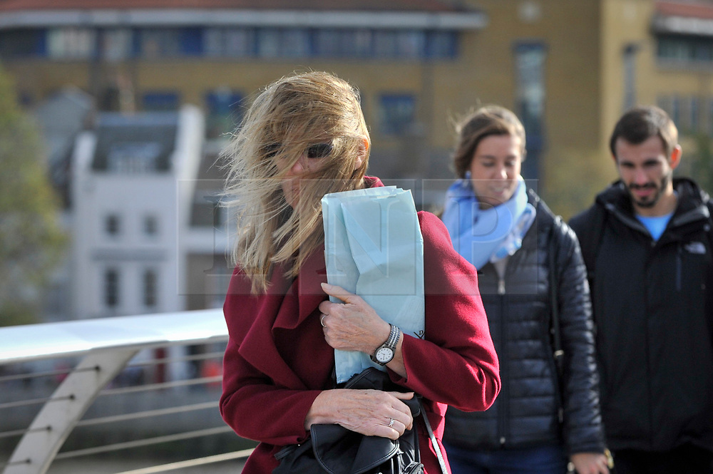 © Licensed to London News Pictures. 21/10/2017. London, UK. Tourists and Londoners are buffeted by gusts crossing the Millennium Bridge as Storm Brian brings windy weather to the capital. Photo credit : Stephen Chung/LNP