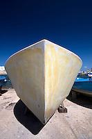 La sagoma dello scafo in vetroresina di una barca in restauro nella darsena del porto di Gallipoli (LE) si staglia imponente sul blu profondo del cielo terso.