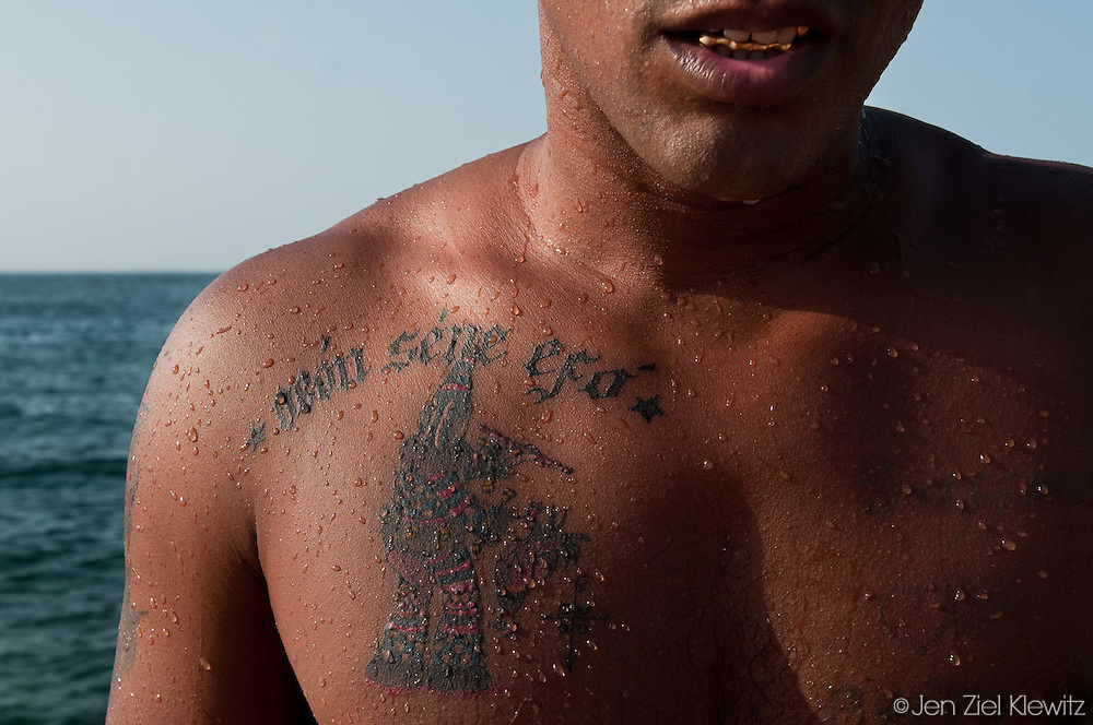 Luis Ramon Lopez Pelegrino emerges from a swim in the ocean along the Malecon (the seafront wall and walkway bordering the city) in Havana, Cuba, displaying a recently-inked tattoo identifying him as a member of the Abakua or Abakuá (various spellings are used). The Abakua is an all-male, initiatory secret society of Afro-Cuban religion. The first such societies were established by Africans in the town of Regla, Havana, in 1836, and this remains the main area of Abakuá presence, including the district of Guanabacoa in eastern Havana. Abakua presence is also strong  in the city of  Matanzas, several hours east of Havana, where Afro-Cuban culture is vibrant. The Abakua societies, whose traditions were brought by African slaves imported to Cuba, are believed to have originated from fraternal associations in the Cross River region of southeastern Nigeria and southwestern Cameroon. Photo by Jen Klewitz