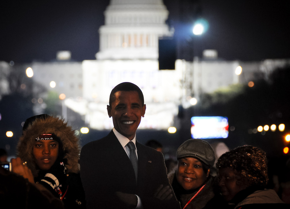 A group of visitors on the National Mall pose for a photo with a life size cutout of President-elect Obama. The US Capitol building where the inauguration ceremony takes place is seen in the rear.