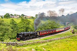 © Licensed to London News Pictures. 18/06/2018. Goathland UK. 1956 BR Standard 4 Tank 80136 travels backwards through the village of Goathland this morning in the North Yorkshire Moors pulling the 10:00 train from Whitby to Pickering. Photo credit: Andrew McCaren/LNP