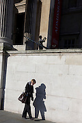 Two women, one using a camera and the other a phone at the National Portrait Gallery in Trafalgar Square.