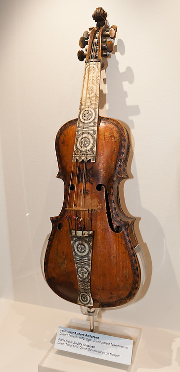 This Hardanger fiddle (hardingfele) was made by Anders Andersen in 1710 or 1810 and is now displayed in the Hardanger Folk Museum, Utne, Norway. In comparison to a standard violin, a Hardanger fiddle is made of thinner wood and adds four or five understrings which resonate with a haunting sound under the four played strings. The Hardanger Folk Museum was founded in 1911 in Utne, Norway.