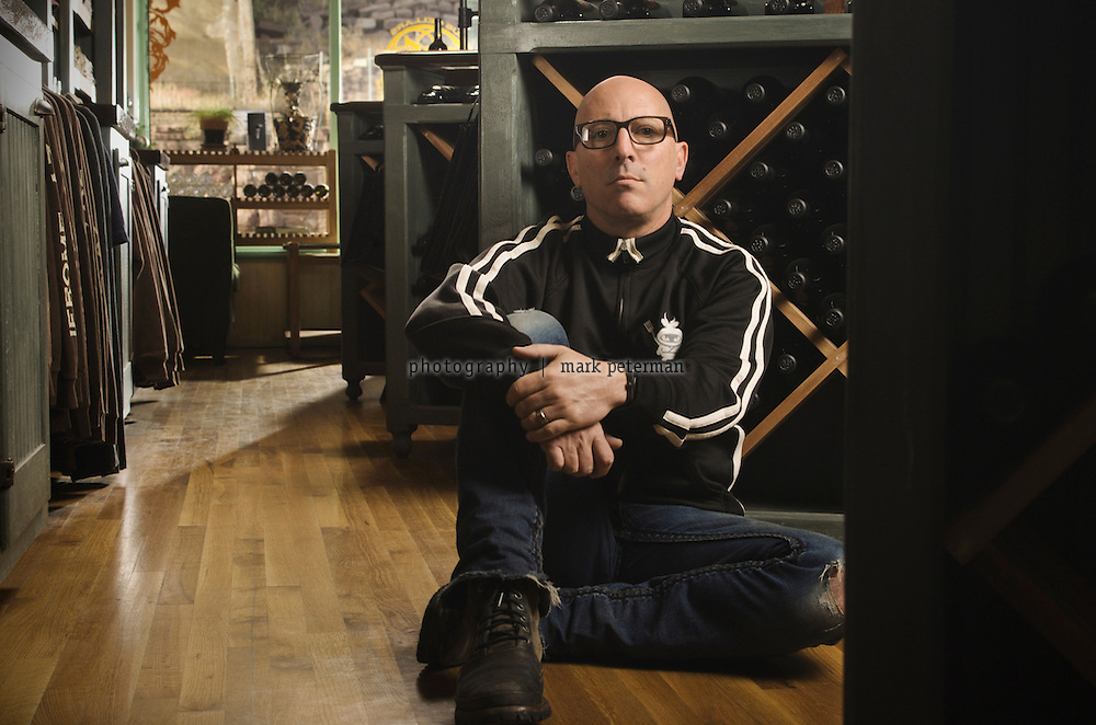 Maynard James Keenan, musician, singer in Tool, A Perfect Circle, Puscifer in front of the storefront, tasting room for Caduceus Cellars and Merkin Vineyards in Jerome, Arizona